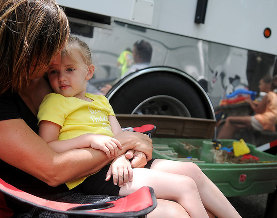 Pam Olsen holds her youngest daughter, Nora, outside the Olsen Custom Farms family mobile home Thursday, June 12, 2014. Chad and Pam Olsen travel with their five children during summer harvest each year. (Staff Photo by BONNIE VCULEK)