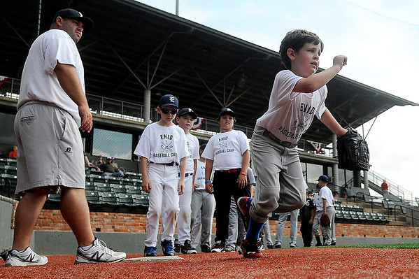 A young baseball enthusiast (right) sprints to first with his glove as Enid High School assistant baseball coach Chris Jensen conducts a base running drill with Enid Baseball Camp participants Tuesday, June 3, 2014. More than 160 youth, both boys and girls, will learn the fundamentals of baseball from 8:30-11:30 a.m. each day during the two week camp at David Allen Memorial Ballpark. Anyone interested in attending the camp may contact Bill Mayberry for more information. (Staff Photo by BONNIE VCULEK)