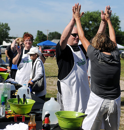 Tossed competitors Randy Wedel and Ebby Stratton high-five at the end of the one-hour cooking period at Enid Farmers Market Saturday, June 21, 2014. Kathy Reihm (far left) won the vegetarian entree contest. (Staff Photo by BONNIE VCULEK)