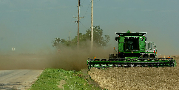 Monday's strong wind blows dust and debris from a combine across Carrier Rd. as it harvests a wheat field. (Staff Photo by BILLY HEFTON)