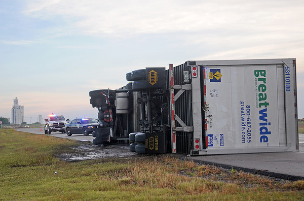 The Oklahoma Highway Patrol investigates the scene of an overturned semi-truck 1.5 miles south of Bison on U.S. 81 Thursday, June 12, 2014. OHP and Garfield County Sheriff Department immediately closed both lanes of the southbound traffic, then reopened the far west lane after the driver of was transported to a local hospital. (Staff Photo by BONNIE VCULEK)