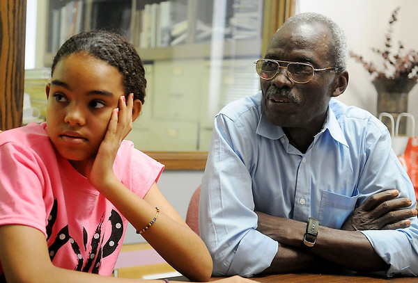 Yacouba Seydou (right), a missionary to Africa, answers a question during an interview at the News & Eagle as his daughter, Sarah, listens Thursday, June 19, 2014. Seydou's missionary work is sponsored by several local churches. (Staff Photo by BONNIE VCULEK)
