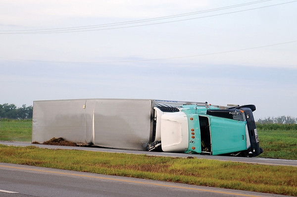 An overturned semi faces north in the southbound lanes of U.S. 81, 1.5 miles south of Bison after the driver of the rig lost control of the vehicle as a severe thunderstorm's sustained winds moved across Garfield County early Thursday, June 12, 2014. Both southbound lanes were closed as Oklahoma Highway Patrol troopers investigated the scene. Once the driver was transported to a local hospital, the inside, southbound lane of U.S. 81 was reopened. (Staff Photo by BONNIE VCULEK)