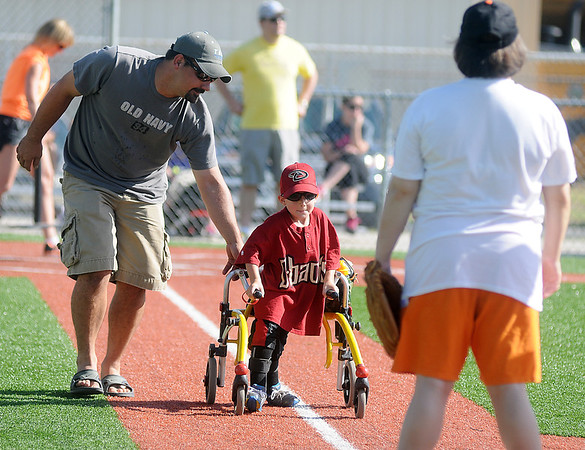 A 4RKids' Miracle League player reaches first base with the help of a buddy at AMBUCS ABC Park Saturday, June 21, 2014. (Staff Photo by BONNIE VCULEK)