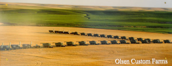 An aerial portrait on the wall of the Olsen family mobile home displays over 30 combines cutting a field of wheat at the same time. Chad and Pam Olsen travel to different harvest locations with their five children each summer. (Staff Photo by BONNIE VCULEK)