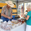 Bailey Rink assists a lady with a honey purchase during GreEnid festivities at Enid Farmers Market Saturday, June 21, 2014. (Staff Photo by BONNIE VCULEK)