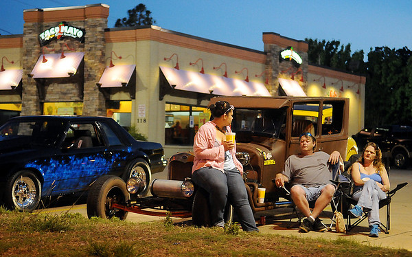 Car enthusiasts relax in the Taco Mayo parking lot after cruising Van Buren Friday, June 13, 2014. Hundreds gather along north and south Van Buren and watch drivers cruise the streets during the two-day event each year. (Staff Photo by BONNIE VCULEK)