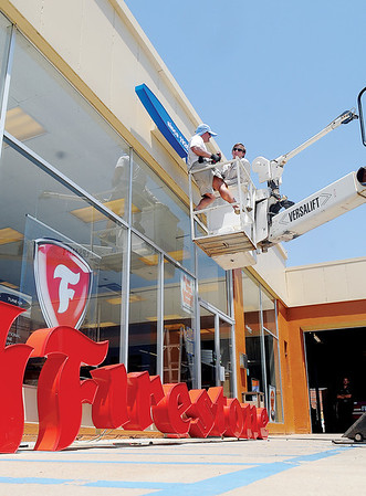 Joe and Jessie Kline (top, from left), from Kline Sign, LLC, install new signage at Firestone Complete Auto Care Wednesday, June 11, 2014. The business located at 117 N. Washington is formerly Expert Tire. (Staff Photo by BONNIE VCULEK