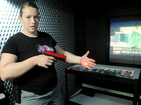 Jennifer Rand, the range master at Bill's Outdoor Sports , discusses the laser and live fire indoor gun range Thursday, June 5, 2014. Brian Lamoreaux, who has owned Bill's Outdoor Sports for four years, had the 42 x 8 foot range built. Individuals or small groups may rent the range for $40 per hour and laser or live fire guns at an additional cost for target or tactical shooting practice. (Staff Photo by BONNIE VCULEK)