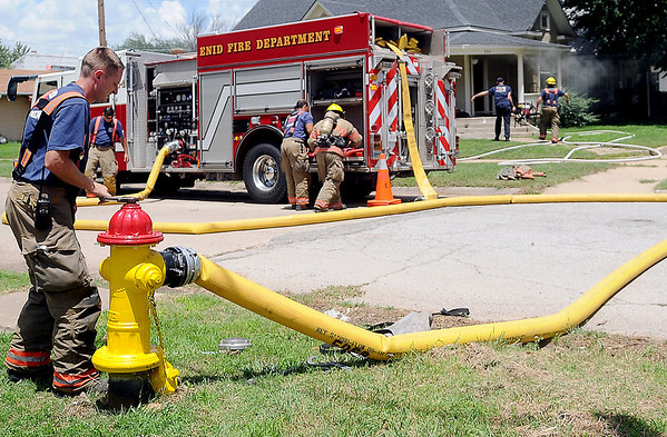An Enid firefighter charges a 6-inch line crews battle a structure fire at 324 W. Pine Saturday, June 21, 2014. (Staff Photo by BONNIE VCULEK)
