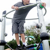 Avron Nix keeps his balance as he turns off a game's light at Meadowlake Park South Thursday, June 26, 2014. (Staff Photo by BONNIE VCULEK)