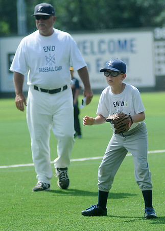 Bill Mayberry (left) encourages young baseball players during the Enid baseball camp at David Allen Memorial Ballpark Tuesday, June 3, 2014. (Staff Photo by BONNIE VCULEK)