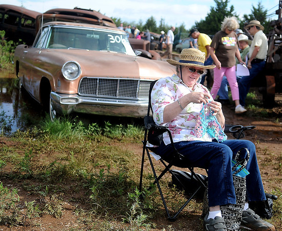 Christine Stark, from San Antonio, Tex, crochets in front of a 1956 Lincoln Continental during the Jordan car auction Saturday, June 7, 2014. (Staff Photo by BONNIE VCULEK)