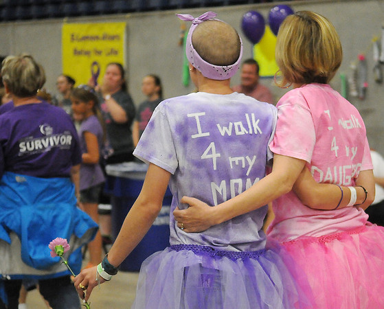 Addi and Kathi Shamburg support each other as they take their victory lap with other cancer survivors during Relay for Life at the Chisholm Trail Coliseum Friday, June 6, 2014. (Staff Photo by BONNIE VCULEK)