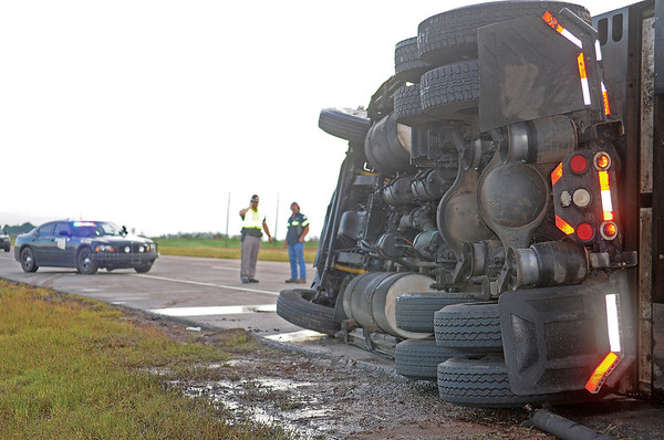 A semi-truck rests on its side as Oklahoma Highway Patrol troopers investigate the cause of the accident 1.5 miles south of Bison on U.S. 81 early Thursday, June 12, 2014. OHP closed a section of the highway and then reopened the inside southbound lane after the driver of the truck was transported to a local hospital. (Staff Photo by BONNIE VCULEK)