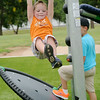 Jayden Goins swings on one of the new games at Meadowlake Park South Thursday, June 26, 2014. (Staff Photo by BONNIE VCULEK)