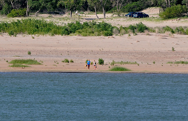 Lake goers make their way to the water edge at Canton Lake Saturday June 21, 2014. The lake level is still down 12 feet from normal after 30,000 acre-feet was released by the Armt Corp of Engineers in early 2013. (Staff Photo by BILLY HEFTON)