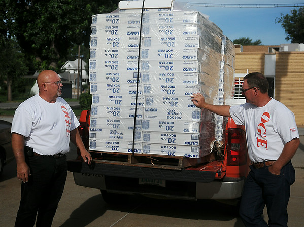 Troy Cowley (left) and Jay Don Hofen, with OG&E, deliver fifty Lasko 20 inch box fans to the Salvation Army. OG&E has assisted with the donation of 1,000 fans to families in need across Oklahoma during the past eight summers. (Staff Photo by BONNIE VCULEK)