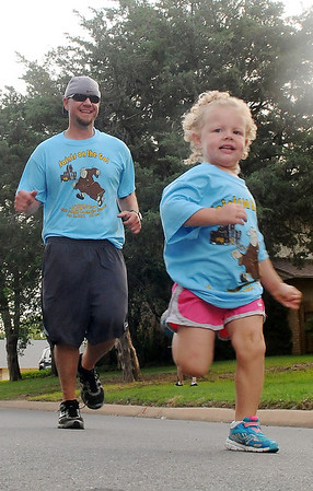 "With a burst of speed, Aisley Carter beats her dad, Eric Carter, across the finish line during the ""Saints on the Go"" family fun run Saturday, June 14, 2014. Eric Carter carried his daughter most of the way until the last block of the race. (Staff Photo by BONNIE VCULEK)"