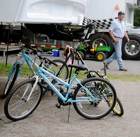 Chad Olsen, a custom harvester with Olsen Custom Farms, walks past his chidren's toys and bicycles as he leaves High Point RV Park to check his clients' wheat. Rain has delayed canola and wheat harvest in Enid and across much of Oklahoma, causing scheduling delays in Olsen's harvest plans. (Staff Photo by BONNIE VCULEK)