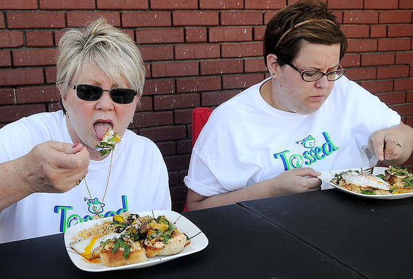 """""""Tossed"""" judges, Barb Benson and Kayte Anton (from left) sample Ebby Stratton's dish during the first round of competition at Enid Farmers Market Saturday, June 21, 2014. (Staff Photo by BONNIE VCULEK)"""