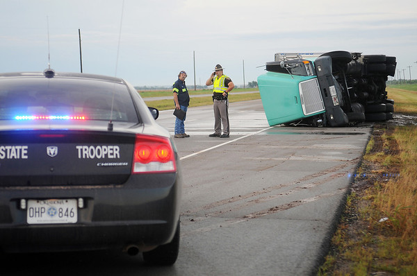 A semi-truck rests on its side as an Oklahoma Highway Patrol trooper investigates an accident 1.5 miles south of Bison on U.S. 81 early Thursday, June 12, 2014. OHP closed a section of the highway and then reopened the inside southbound lane after the driver of the truck was transported to a local hospital. Oklahoma Highway Patrol, Garfield County Sheriff Department, Life EMS and Stanley's Wrecker Service assisted at the scene. (Staff Photo by BONNIE VCULEK)