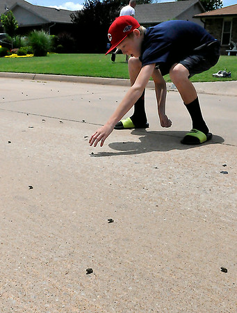 Miles Atherton catches frogs in the middle of Wellington St. Monday. Thousansa of the tiny frogs appeared to come from a retention pond being built west of Wellington Street and moving through the neighborhood. (Staff Photo by BILLY HEFTON)