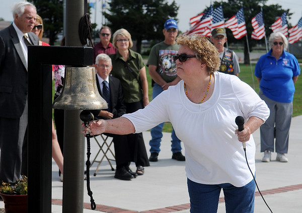 """Karen Vollman rings a bell as she remembers her late husband, U. S. Navy Seaman Richard David Vollman, during the Unsung Hero """"In Memory"""" Ceremony on Flag Day at the Vietnam Memorial Wall and Woodring Wall of Honor Veterans Park Saturday, June 14, 2014. Vollman was a Navy mechanic during the Vietnam War and died in August 2002, of leukemia at the age of 52. The service honored men and women who died indirectly from their service in Vietnam. (Staff Photo by BONNIE VCULEK)"""