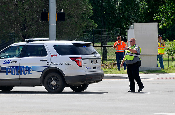 An Enid police officer directs traffic at the intersection of Willow & Oakwood Monday as maintenance crews work on the traffic signals. (Staff Photo by BILLY HEFTON)