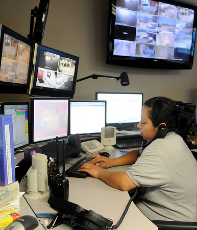Erica Moses fields a 911 call at Enid Garfield County Major County 911 Communications in the Enid Police Department Wednesday, June 11, 2014. Moses, who has been a 911 communications supervisor for 4 years, uses split ear listening skills to successfully do her job. (Staff Photo by BONNIE VCULEK)