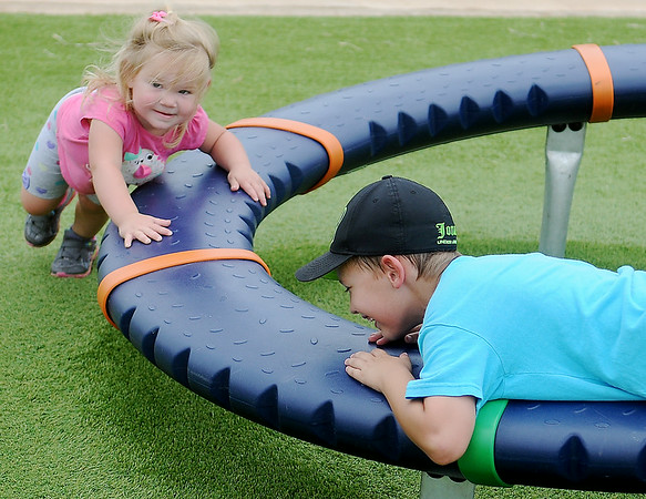 Little Madisyn Goins (left) pushes Jonan Nix on one of the new games at Meadowlake Park South Thursday, June 26, 2014. The city of Enid Parks and Recreation employees have helped install new playground equipment around Enid. (Staff Photo by BONNIE VCULEK)