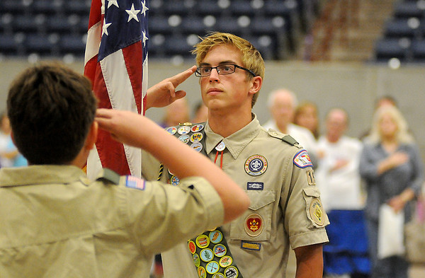 Cannon Cribley and Jake Taylor (from left), with Boy Scouts of America Troop 15 in Enid, salute as Douglas Conrady plays the National Anthem during Relay for Life opening ceremonies at the Chisholm Trail Coliseum Friday, June 6, 2014. (Staff Photo by BONNIE VCULEK)