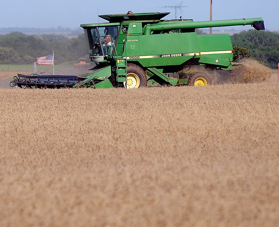 An American flag flies in the distance as an area farmer harvests his wheat near Longhorn Road and U.S. Highway 81, south of Enid, Saturday, June 14, 2014. (Staff Photo by BONNIE VCULEK)