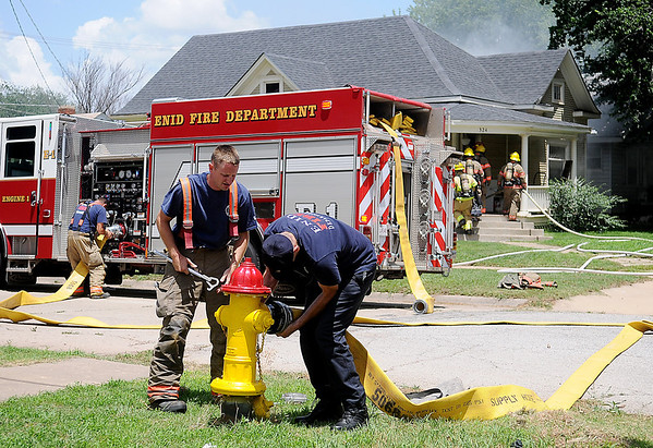 Enid firefighters connect a 6-inch line to a hydrant as others enter a structure fire at 324 W. Pine Saturday, June 21, 2014. (Staff Photo by BONNIE VCULEK)