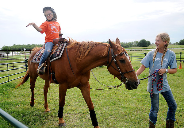 Gracie Hitt meditates in the saddle atop Uriah as Elisa Salyer leads the gentle horse around the ring during Enter His Gates Summer Camp at Wes Madison's home southeast of Garber Friday, June 20, 2014. Participants, age 7 and up, enjoy canoeing, fishing, science exploration, Amazing Race art sessions and horseback riding. (Staff Photo by BONNIE VCULEK)
