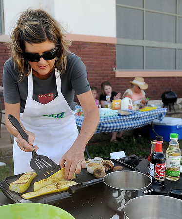 """Ebby Stratton grills yellow squash, mushrooms and onions during the first """"Tossed"""" competition at Enid Farmers Market Saturday, June 21, 2014. Stratton, Kathy Reihm and Randy Wedel prepared an entree in one hour before the judging began. (Staff Photo by BONNIE VCULEK)"""