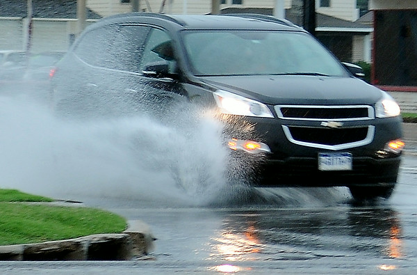 The driver of a Chevrolet SUV drives through standing water as a severe thunderstorm moves across much of Northwest Oklahoma Saturday, Feb. 28, 2014. Several streets in different residential areas and right lanes along Van Buren and Owen K. Garriott were treacherous for Enid drivers until the rain subsided. (Staff Photo by BONNIE VCULEK)