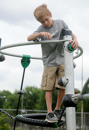 Ethan Davis turns off a flashing light as he plays a game at Meadowlake Park South Thursday, June 26, 2014. (Staff Photo by BONNIE VCULEK)
