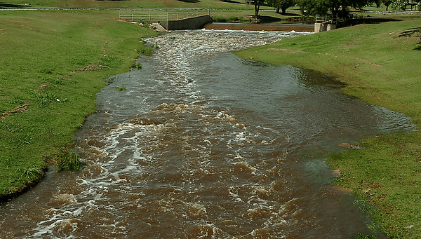 Water rushes over the dam at Meadowlake Park Monday. (Staff Photo by BILLY HEFTON)