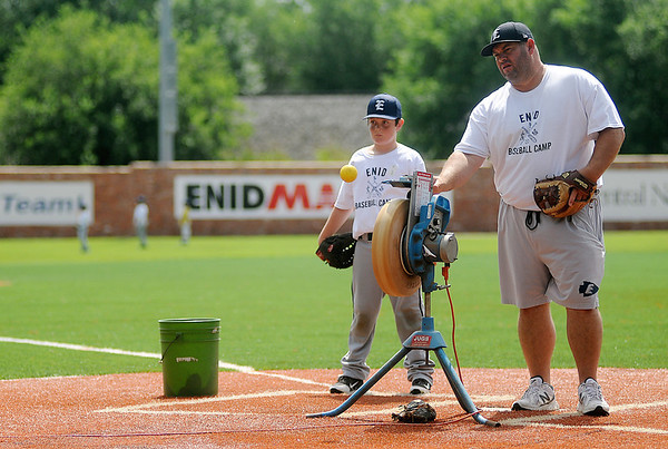 Enid High School assistant baseball coach, Chris Jensen, launches a ball using a pitching machine at the Enid baseball camp Tuesday, June 3, 2014. (Staff Photo by BONNIE VCULEK)
