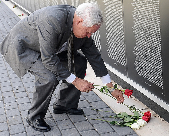 """Capt. Pat Healy, U.S. Air Force Reserves, Retired, places five roses near the base of the Vietnam Wall honoring five of his friends during the Unsung Hero """"In Memory"""" Ceremony Saturday, June 14, 2014. Healy and Phil Templin, who flew a C123 during the Vietnam War, placed a memorial wreathe at the apex of the Vietnam Memorial Wall. (Staff Photo by BONNIE VCULEK)"""