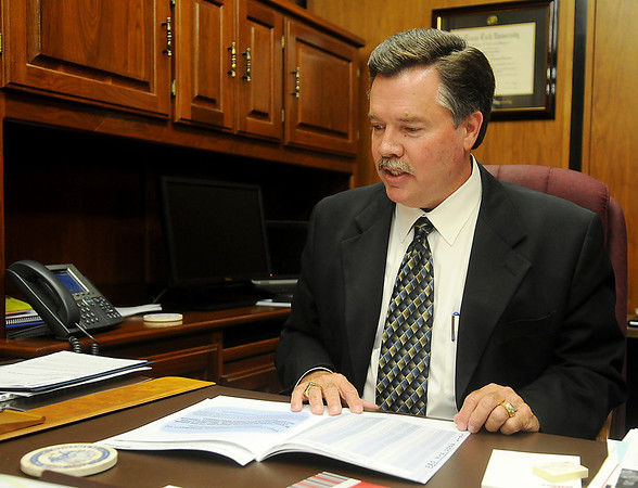 Dr. Darrell Floyd, the new superintendent for Enid Public Schools, peruses paperwork in his office Tuesday, June 10, 2014. (Staff Photo by BONNIE VCULEK)