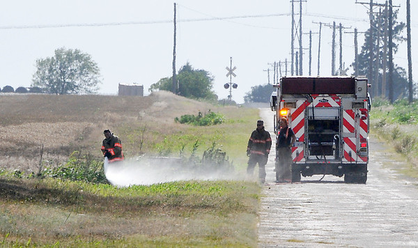 Firefighters hit a hot spot on the edge of a wheat field along east Market Wednesday. Units from Breckinridge, Fairmont and Enid responded to the fire that burned an estimated 40 acres. (Staff Photo by BILLY HEFTON)