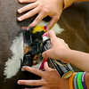 Enter His Gates summer campers use water-based spray paint and glitter as they decorate their favorite horses on the final summer riding session Friday, June 27, 2014. (Staff Photo by BONNIE VCULEK)
