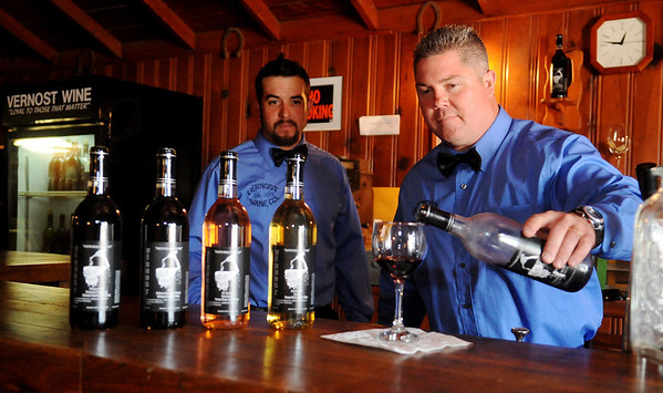 Zach Hardin (left) watches as Dagan Hardin (right) pours a glass of Vernost Wine for a customer at 110 N. Main in Hennessey Saturday, June 7, 2014. Wes Hardin, Zach Hardin and Dagan Hardin started the business last year and celebrated the grand opening Friday evening at their new location. (Staff Photo by BONNIE VCULEK)