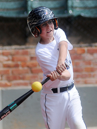 A young batter concentrates as he connects with a machine-pitched ball during the Enid Baseball Camp at David Allen Memorial Ballpark Tuesday, June 3, 2014. (Staff Photo by BONNIE VCULEK)