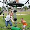 Samantha Goins (bottom, left) and her son, Jayden, race toward a flashing light as they play a game with Ethan Davis (top left) and Avron Nix at Meadowlake Park South Thursday, June 26, 2014. (Staff Photo by BONNIE VCULEK)