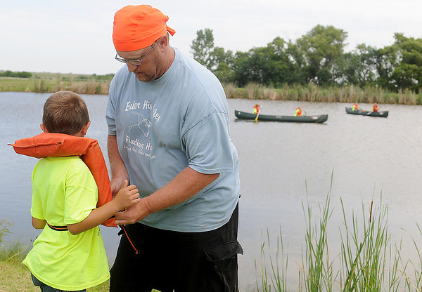 """Getty Chance (front, right), an Enter His Gates canoeing instructor, helps Brandon Buffallo with his life vest as others maneuver around the quiet lake setting Friday, June 20, 2014. Doris Williams began the summer camp seven years ago. With the help of several volunteers, more than 100 children experience horseback riding and proper care for horses, canoeing, science investigation, and """"Amazing Race"""" art. (Staff Photo by BONNIE VCULEK)"""