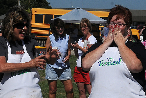 "Ebby Stratton (left) and Kathy Reihm react as Reihm wins the ""Tossed"" competition at Enid Farmers Market Saturday, June 21, 2014. (Staff Photo by BONNIE VCULEK)"