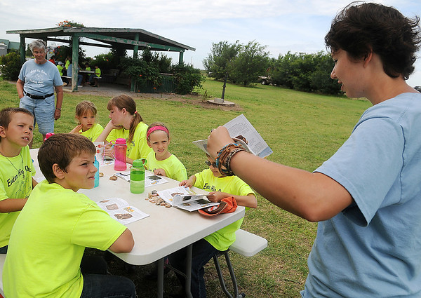 Sara Garis (right), a zoology major from Oklahoma State University, discusses the different types of rocks during Enter His Gates summer camp Friday, June 20, 2014. Doris Williams (back, left) started the camp seven years ago. Children, ages 7 and up, enjoy horseback riding, canoeing, fishing, science investigation and creative arts during the Christian-based camp. Several area churches and generous individuals provide financial support for the program each year. (Staff Photo by BONNIE VCULEK)